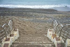 escaleras de hormigón que conducen a una playa y cuerpo de agua foto