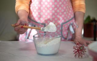 Woman mixing flour in a glass bowl with a pink apron at home