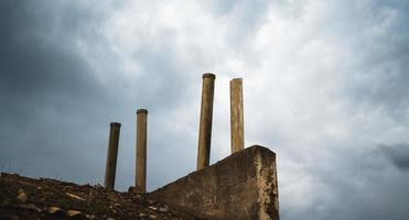 Chimneys on a ruined roof with a dramatic storm sky photo
