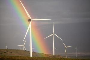 Wind power mills in a storm with cloudy gray skies and a rainbow