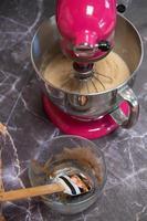Recipiente con chocolate junto a una batidora sobre un fondo de mármol oscuro foto