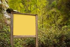 Mockup of wooden sign in nature after rain photo