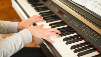 Woman's hands learning piano photo