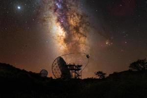 Radio telescope with the galactic center behind it photo