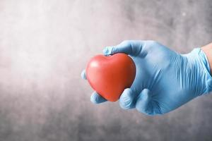Gloved hand holding a red heart photo