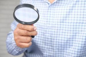 Man holding a magnifying glass photo