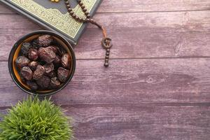 Quran with rosary and dates photo