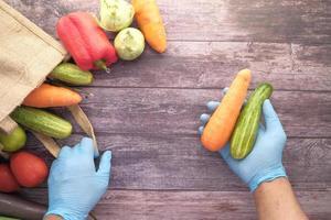 Person wearing gloves handling vegetables