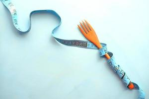 Fork with measurement tape on blue background