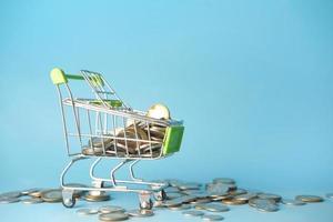 Monedas en un carrito de compras sobre fondo azul. foto