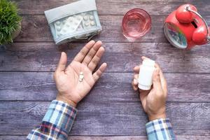 Person taking pills flat lay