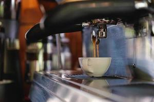 Espresso pouring into cups photo