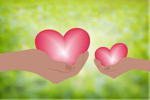 Hand holding heart.Give a pink heart with love.blurred green background vector