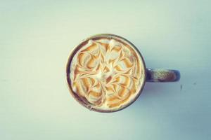 taza de macchiato de caramelo con leche caliente foto