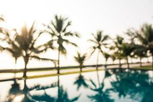 Abstract blur outdoor swimming pool with coconut palm trees photo
