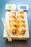 Salmon fish meat sushi roll maki on wood plate photo