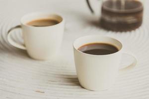 Punto de enfoque selectivo en café negro en taza blanca foto
