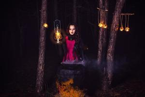 Girl alone at night in the forest brews a potion and wonders for marriage photo