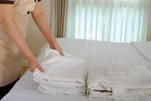 Joven sirvienta arreglando la toalla y haciendo la cama en la habitación del hotel foto