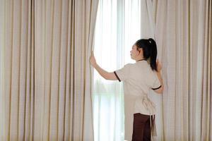 Joven sirvienta abriendo cortinas en la habitación del hotel foto