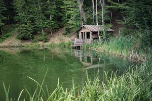 una cabaña junto a un lago rodeado de árboles en yalta, crimea foto