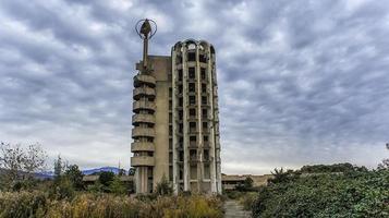 Un alto edificio abandonado con un cielo azul nublado en la aldea de Esher, Abjasia foto