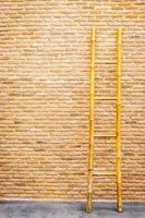 Wood ladder on brick wall background photo