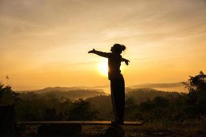 Silhouette of free cheering woman with open arms at mountain peak sunrise photo