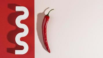 Red pepper on red and white background photo