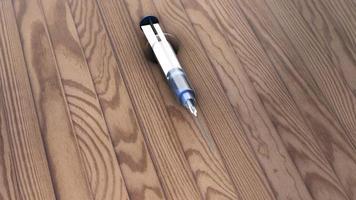 animierte Impfstoffspritze auf einem Holztisch liegend