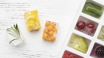 Top view assortment of frozen fruit in an ice tray