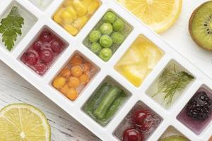 Flat lay assortment of frozen fruit in an ice tray