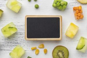 Flat lay of chalk board and frozen fruit and vegetables photo