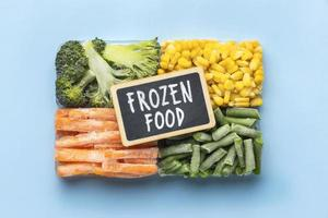 Verduras congeladas sobre fondo azul. foto