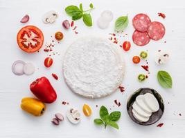 Ingredients for homemade pizza on white wooden background photo