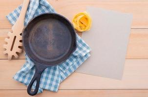 Food background for tasty Italian dishes with empty cast iron skillet and pasta ladle
