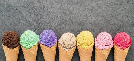 Flat lay various of ice cream cones set up on dark stone background photo