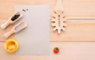 Blank paper and pasta ladle on wooden background photo