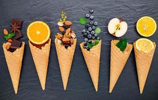 Various ingredients for ice cream flavor in cones on dark stone background photo