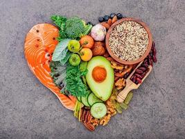 Ingredients for healthy foods selection on dark stone background in heart shape photo