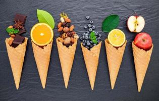 Various ingredients for ice cream flavors on dark stone background photo