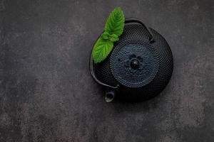 Black cast iron tea pot with herbal tea set up on dark stone background