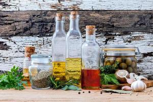 Different sorts of cooking oils on old wooden background