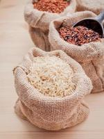Mixed whole grain traditional thai rices in hemp sacks bag setup on wooden background