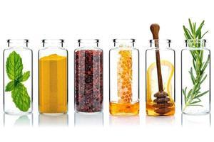 Botellas de vidrio de cuidado de la piel y exfoliantes corporales caseros con ingredientes naturales sobre fondo blanco. foto