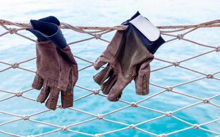 Sailing gloves hanging on the nets of sailing yacht