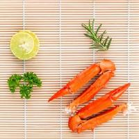 Boiled crab claws with lime and parsley on bamboo background photo