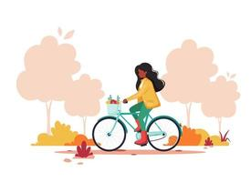 Black woman riding bike in autumn park. Healthy lifestyle, sport, outdoor activity concept. Vector illustration.
