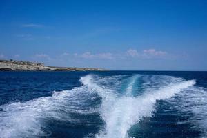 Vista de la estela de un barco en el agua con el cielo azul nublado foto