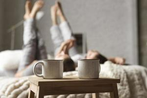 Coffee cups on table with couple in bed